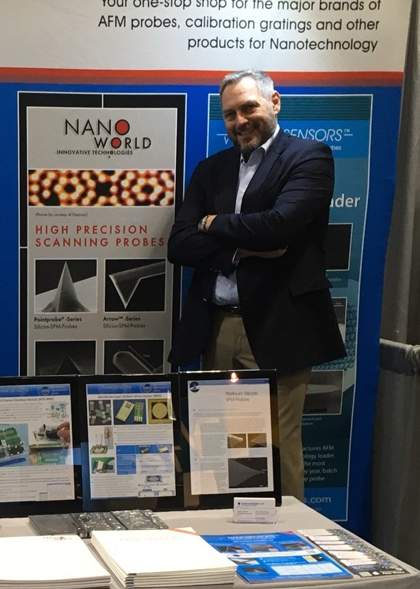Manfred Detterbeck CEO of NanoWorld AG in front of NanoWorld AFM probes poster at booth 610 at 2017 MRS Fall Exhibit